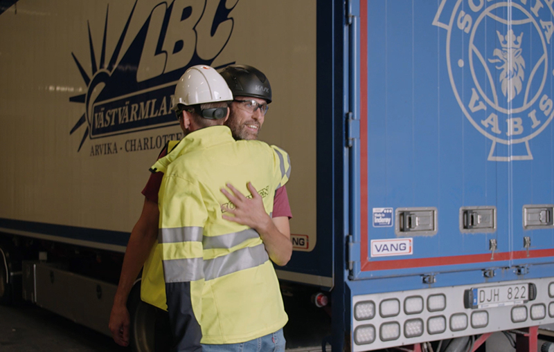 Fredric and Lars Kristen hug in front of the lorry six months after the accident.